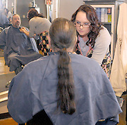 gbs121213a/ASEC -- Audrey Morelock trims the goatee of her father, John Morelock, before cutting off his long hair  at the Hair Addict salon on Thursday, December 12, 2013. The braided locks with be donated to Pantene Beautiful Lengths which gives free wigs to adult cancer victims.(Greg Sorber/Albuquerque Journal)
