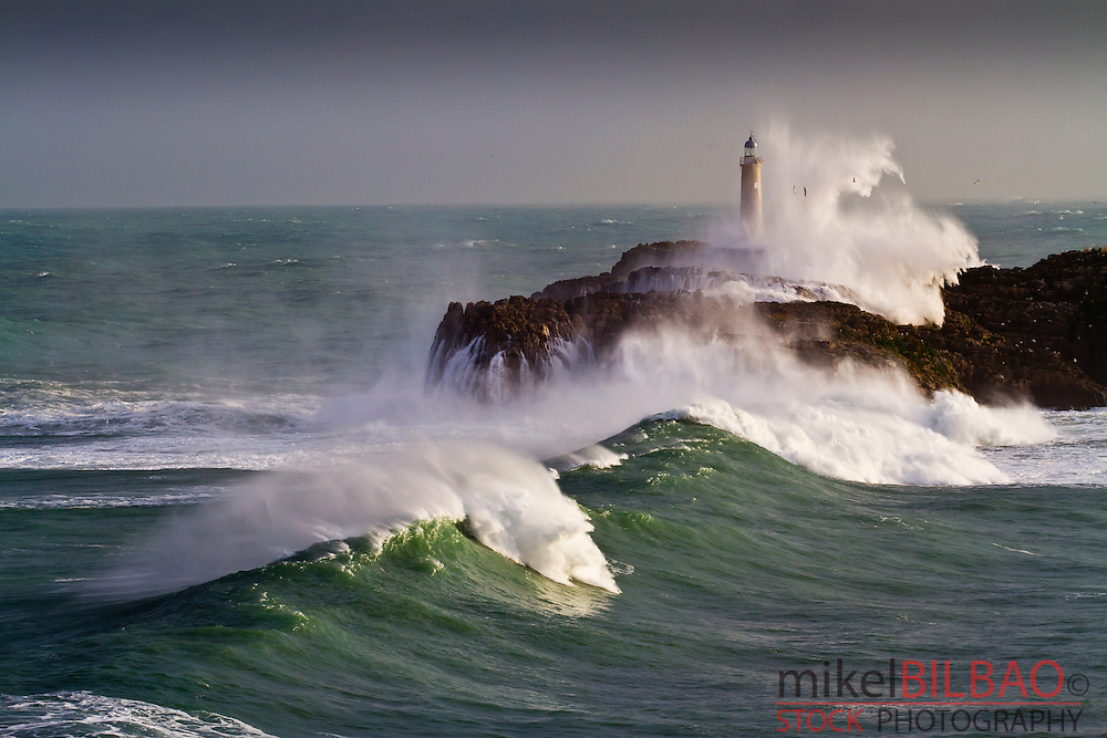 Mouro island and lighthouse in a storm. .Santander. Cantabria, Spain.