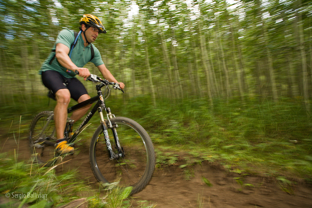 A mountain biker pedals on single-trak near Nederland, Colorado in summer time.