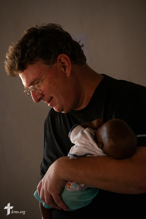 The Rev. Michael Awe, team leader and pastor at Hope Lutheran Church, South Sioux City, Neb., spends a few joyful moments holding an infant on the third day of the LCMS Mercy Medical Team on Wednesday, May 9, 2018, in the Yardu village outside Koidu, Sierra Leone, West Africa. LCMS Communications/Erik M. Lunsford