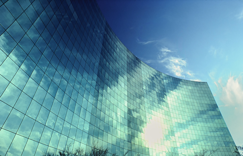White Clouds And Blue Sky Reflect In Glass Office Building
