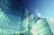 Blue sky and white clouds reflected in glass office building windows.