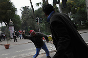 A protester throws a stone to the police during a  demonstration in the center of Tunis. People still protest against the partecipation of the Constitutional Democratic Rally, RCD, party of Ben Ali, to the national unity government that today january 18 lost three ministers of the opposition.