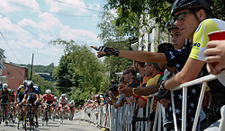 "Manayunk Wall Bike Race Day, Philadelphia, PA USA - June 3 2012; A cycling fan points out a professional rider from the peleton as they climb the steepest part of the course. The 'Manayunk Wall"" at Lyceum Avenue reaches a peak incline of 17% at some points. <br /> <br /> ( Nikon D2X 