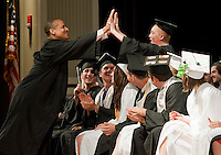 Keynote speaker Brian Stuart gives a high five to Andrew Long during Prospect Mountain High School's Commencement Friday evening.  (Karen Bobotas/for the Concord Monitor)