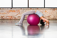 A young woman stretching in a backbend over a exercise ball.