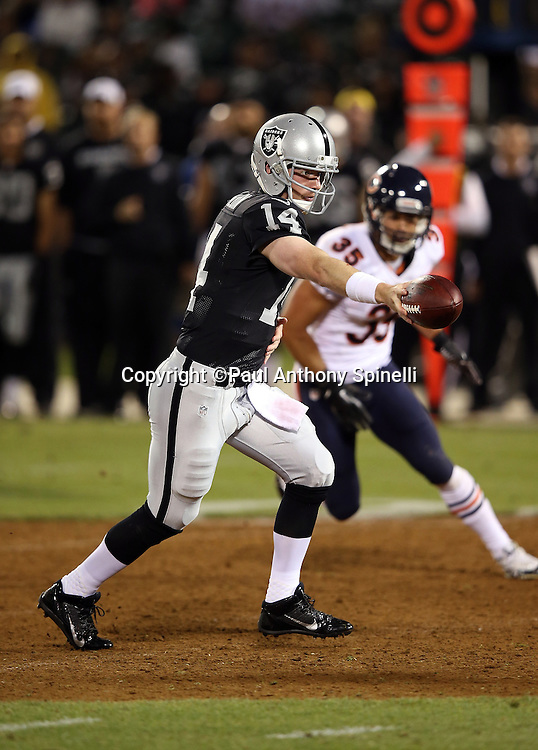 Oakland Raiders quarterback Matthew McGloin (14) hands off the ball on a running play during the NFL preseason week 3 football game against the Chicago Bears on Friday, Aug. 23, 2013 in Oakland, Calif. The Bears won the game 34-26. ©Paul Anthony Spinelli