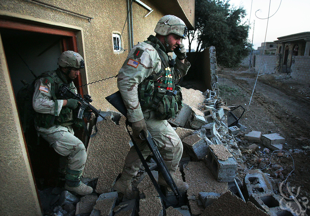 U.S. Army 1st Infantry Division 2nd Battalion-2nd Regiment Staff Sergeant Benjamin Richey (r) from Mart ,Texas receives radio instructions as his squad conducts a neighborhood sweep of remaining insurgent fighters November 12, 2004 in the Iraqi insurgent stronghold of Fallujah.
