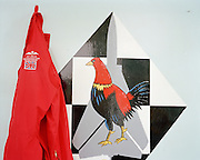 Red flying suit belonging the Red Arrows, Britain's RAF aerobatic team, hanging near another Squadron's cock emblem