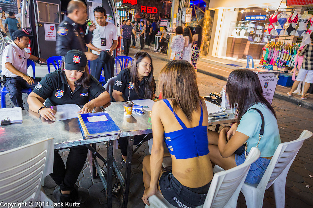 "26 SEPTEMBER 2014 - PATTAYA, CHONBURI, THAILAND: Tourist police process ""katoeys"" or Ladyboys, (the Thai term for a transgendered prostitute) on Walking Street in Pattaya. Pataya, a beach resort about two hours from Bangkok, has wrestled with a reputation of having a high crime rate and being a haven for sex tourism. After the coup in May, the military government cracked down on other Thai beach resorts, notably Phuket and Hua Hin, putting military officers in charge of law enforcement and cleaning up unlicensed businesses that encroached on beaches. Pattaya city officials have launched their own crackdown and clean up in order to prevent a military crackdown. City officials have vowed to remake Pattaya as a ""family friendly"" destination. City police and tourist police now patrol ""Walking Street,"" Pattaya's notorious red light district, and officials are cracking down on unlicensed businesses on the beach.     PHOTO BY JACK KURTZ"