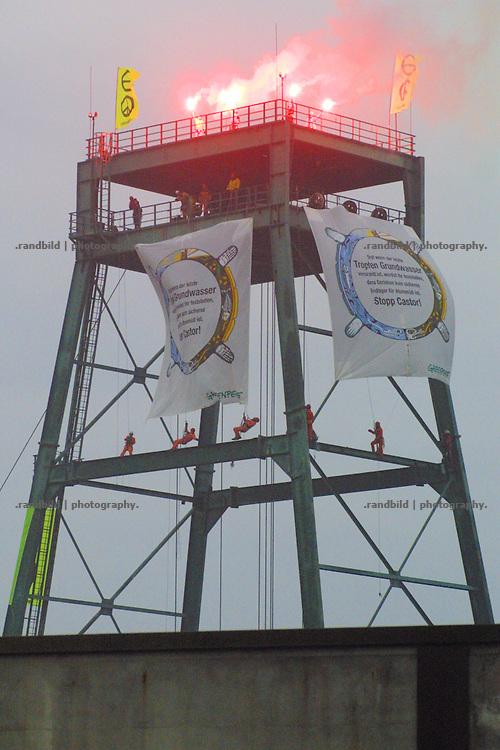 Greenpeaceaktivisten haben den Turm von Schacht 2 des Erkundungsbergwerkes in gorleben besetzt. Mit roten Fackeln machen sie im Morgengrauen auf isch aufmerksam.