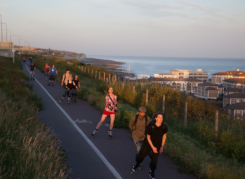 Every Tuesday evening in summer, a group of enthusiastic rollerbladers gather for a fast-paced ride around town. With several participants offering different styles of music, a joyful party mood is created. Here they can be seen utilising one of the city's many lanes dedicated to cycles and skaters, with the marina below in the distance.