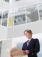 Business woman reading newspaper in atrium of office building low angle view