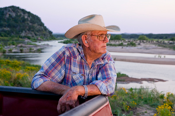 Stock photo of an older cowboy leaning on his truck enjoying the sunset along the Llano River in the Texas Hill Country