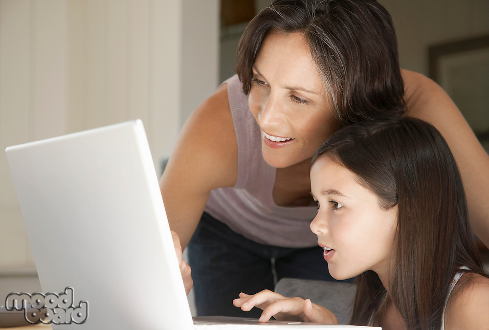 Mother helping daughter use laptop sitting at home