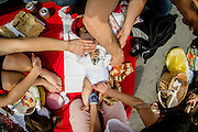 "A pic nic was held on the street in the center of Brussels, to ""reclaim the streets and the public place"". Hundreds picnicked to demand a carfree citycenter. The event was not officially permitted. A child is being changed his diper. this image is part of a series of 8 shot from above in wide angle focus on food"