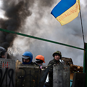 KIEV, UKRAINE - February 20, 2014: Anti-government protestors take cover behind newly build barricades at the frontline where violent clashes were happening between protestors and riot police outside Independence Square in central Kiev. The riot police responded to the advance with gunfire that, according to the opposition, killed at least 70 and as many as 100 people. The drastic escalation of the three-month-old Ukraine crisis left the country reeling from the most lethal violence in decades. CREDIT: Paulo Nunes dos Santos