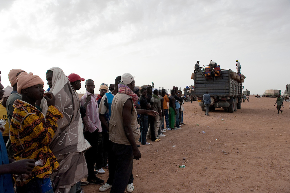 Young African migrants standing in front of the truck which will bring them to Dirkou through the Ténéré desert