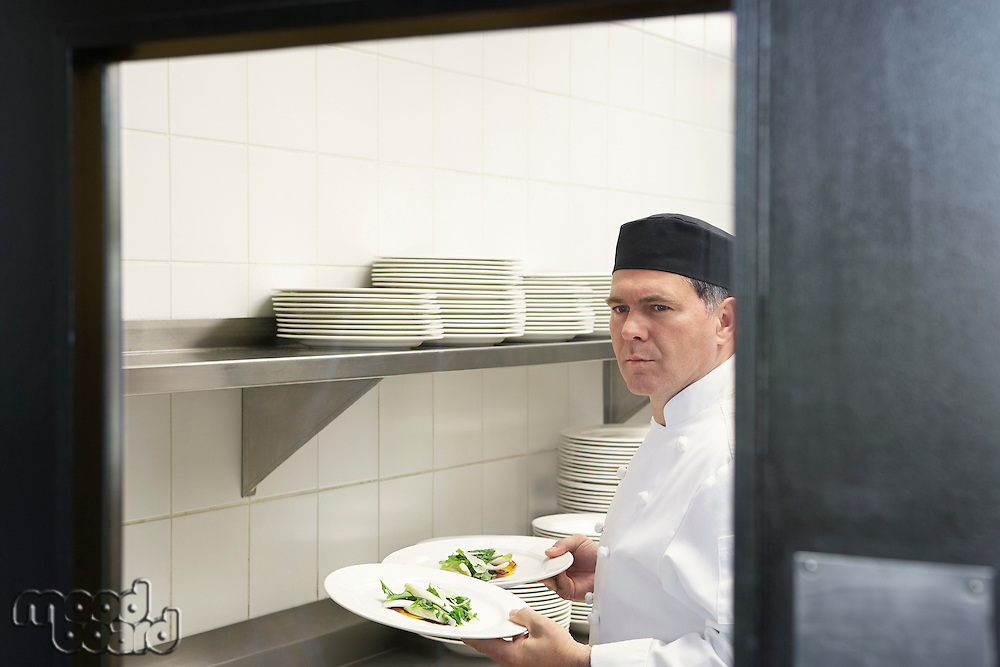 Man chef holding plates of food in kitchen