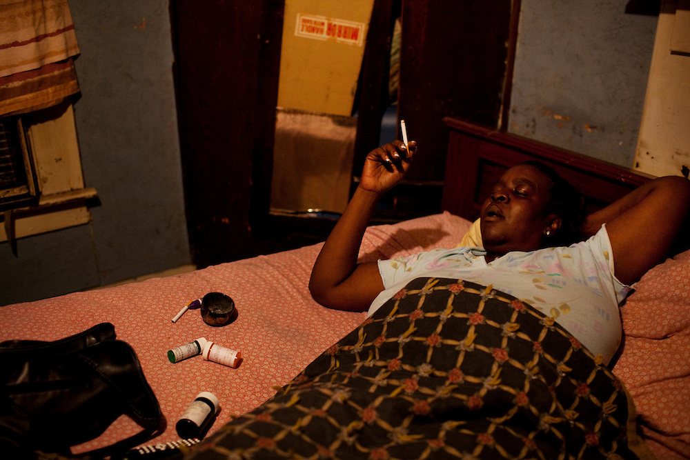 """Ellen """"El"""" Wilson lies in bed smoking a cigarette a few months after suffering a stroke in the Baptist Town neighborhood of Greenwood, Mississippi on Thursday, November 4, 2010. Daily she must deal with a number of health issues including her sciatic nerve laying on her spine, which makes it difficult for her to walk. Her children Jabari and Nikki work to support their mother who applied for SSI in 2006 but has allegedly still not received anything."""