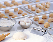 Baking sheets covered with dinner rolls form the background for raw dough, eggs and a rolling pin in an institutional kitchen.