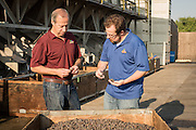 Keith and Matt Jura discuss the latest batch of figs in front of the fig sorting machine at the Nutra Fig plant in Fresno, California.