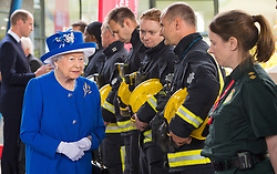 Queen Elizabeth II meets firefighters and paramedics during a visit to the Westway Sports Centre, London, which is providing temporary shelter for those who have been made homeless in the Grenfell Tower disaster.