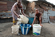 A girl watches while a woman draws water from a well in the West Point slum in Monrovia, Montserrado county, Liberia on Monday April 2, 2012.