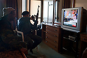 "Libyan rebel fighters watch television news in a hotel room for the latest info on their war with pro-Qadaffi forces March 07, 2011 in Ras Lanouf, Libya. The fighters ""liberated"" the hotel in Ras Lanouf that morning and have been using it as their defacto HQ ever since."