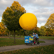Free ice cream and a yellow ballon on a tricycle in Victoria Park. The charity 1010 campaigns for awareness of the proposed cuts to solar energy subsidies. The cuts by up 90% proposed by the UK government will put a stop on any future solar panel installations in the UK.
