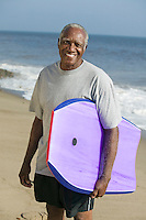 Senior man holding surfboard