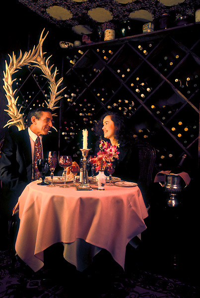Stock photo of a man and woman sitting at a private table in front of the wine wall
