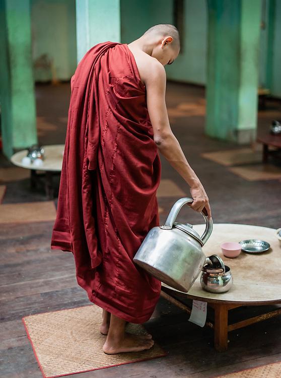 Buddhist monk serving tea at Kha Khat Wain Kyaung Monastery Dining Room (Bago, Myanmar).