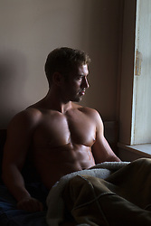 good looking shirtless man in bed looking out the window