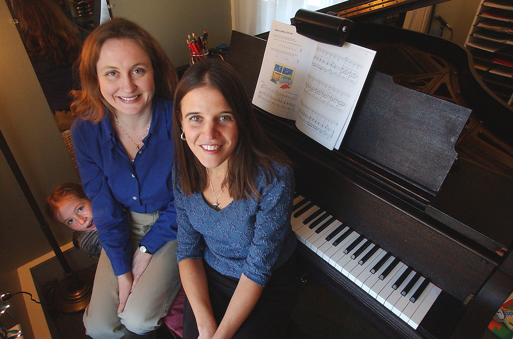 Gloucester: Annette Dion, right and Julie Cleveland, run the Cape Ann Piano Studio. Peaking around them is one of their students, Madison Adams Poore, 5. ((((this all I know about this story for Richard))))))))) (Photo by Mike Dean/Gloucester Daily Times). Monday, January 27, 2003 (NOTE: THIS IS A DIGITAL CAMERA IMAGE)..**************************************.Filter: Min (QMPro: Red Radius:0/Blue Radius:3/No Desp.).USM: Normal (Amt:200/Radius:0.3/Thresh:2).File Size: 7.56MB.Original file name: DSC_1764.JPG