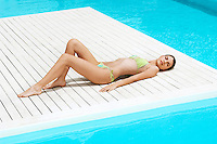 Young Woman Sunbathing on deck by swimming pool high angle view