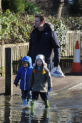 © Licensed to London News Pictures. 19/01/2014. Children in wellies walk through flood water. The town of Eynsford in Kent flooded where the river Darent has broken it's banks after overnight rain caused river levels to rise. Photo credit :Grant Falvey/LNP