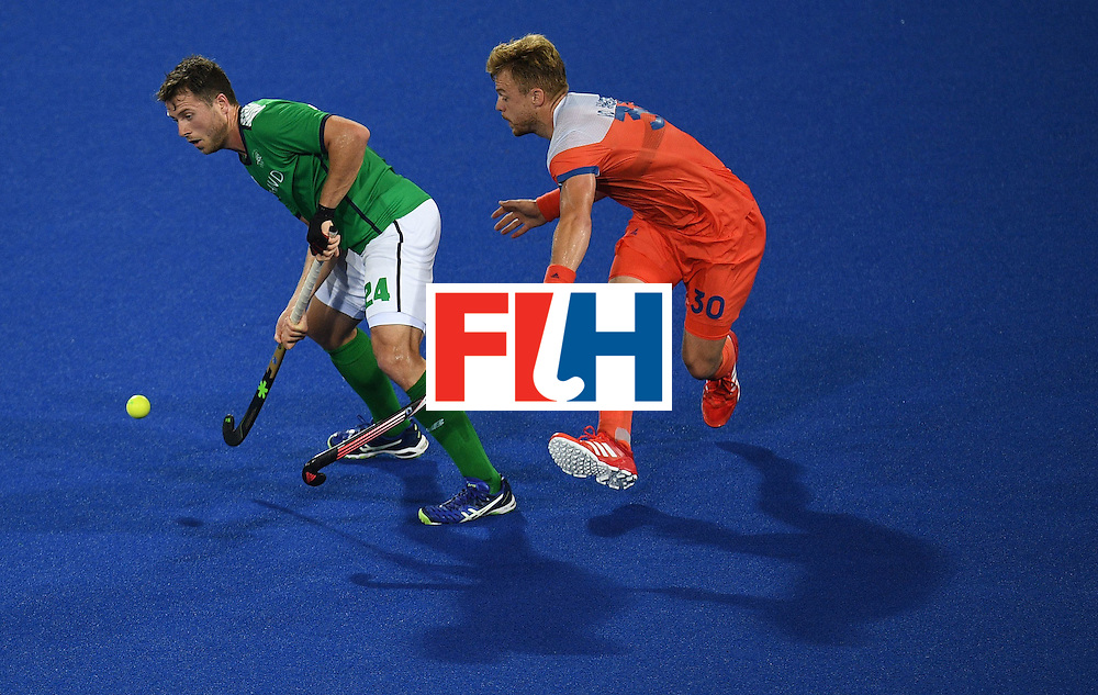 Ireland's Kyle Good (L) vies for the ball with the Netherland's Mink van der Weerden  during the men's field hockey Netherlands vs Ireland match of the Rio 2016 Olympics Games at the Olympic Hockey Centre in Rio de Janeiro on August, 7 2016. / AFP / MANAN VATSYAYANA        (Photo credit should read MANAN VATSYAYANA/AFP/Getty Images)