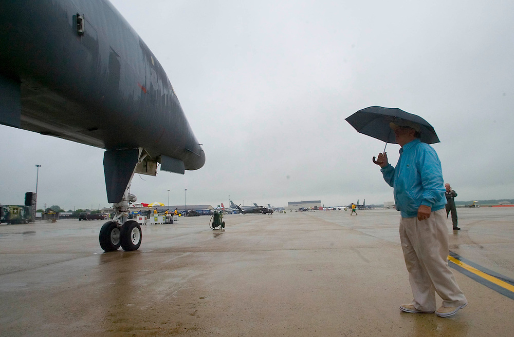 (PSUNDAY) McGuire AFB 6/4/2004 Mike Morollo of Long Beach Island stands under his umbrella as he look at a B-1 Bomber on display at the McGuire Air Show.   EDS:  Due to weather the in air performances were either cancelled or delayed indefinitely until the conditions made it safe to fly. Please also note the crowds were VERY thin.  I did the best I could.   Michael J. Treola Staff Photographer....MJT