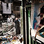 """Mujeres de origen copto clasificando basura en las calles de Mokattam . En medio del barrio de Manshiet Nasr a las afueras de El Cairo esta situado el asentamiento de Mokattam conocido como la """"Ciudad de la Basura"""" , está habitado por los Zabbaleen ,una comunidad de unos 45.000 cristianos coptos que viven desde hace varias décadas de reciclar los desperdicios que genera la capital egipcia: plástico, aluminio, papel y desechos órganicos que transforman en compost . La mayoría forman parte de la Asociación para la Protección del Ambiente (APE) una ONG que actúa en el área, cuyos objetivos son proteger el medio ambiente y aumentar el sustento de las recuperadores de basura de El Cairo. Según la ONU, el trabajo que se realiza en Mokattam como uno de los diez mejores ejemplos del mundo en el mejoramiento medioambiental. El Cairo , Egipto, Junio 2011. ( Foto : Jordi Camí )"""