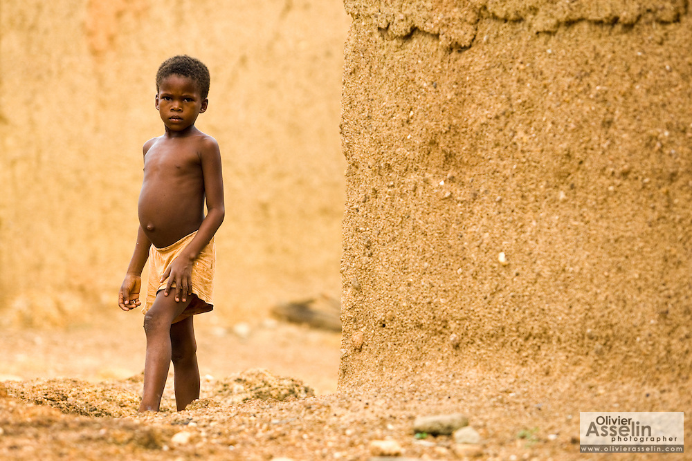 Young boy standing among mud houses in Tano Akakro, Cote d'Ivoire on Saturday June 20, 2009.