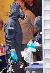 © Licensed to London News Pictures. 06/07/2018. Amesbury, UK. Police in protective suits and gas masks gather evidence at the house where a couple, named locally as Dawn Sturgess, 44, and her partner Charlie Rowley, 45, were taken ill on Saturday 30th June 2018. Police have confirmed that the couple have been in contact with Novichok nerve agent. Former Russian spy Sergei Skripal and his daughter Yulia were poisoned with Novichok nerve agent in nearby Salisbury in March 2018. Photo credit: Peter Macdiarmid/LNP