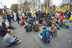 © Licensed to London News Pictures. 14/03/2018. LONDON, UK.  Around a hundred pro-Kurdish protesters waving YPG flags stage a sit-in on Parliament Square blocking traffic for over three hours. The group is aiming to highlight Turkish attacks on Kurdish held Afrin in northern Syria and has previously targeted train stations in London and Manchester. Photo credit: Cliff Hide/LNP