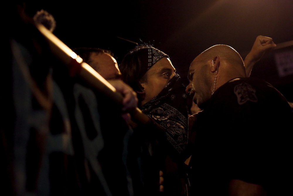 A mediator talks to protesters as they face off with law enforcement during an unscheduled silent march against police brutality during the 2012 Republican National Convention on August 29, 2012.