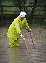 © Licensed to London News Pictures. 26/11/2012..Boulby, North Yorkshire..A worker from Redcar and Cleveland Highways department tries to clear blocked drains on the main road between Easington and Staithes following another night of heavy rain that caused disruption in parts of East Cleveland and North Yorkshire...Photo credit : Ian Forsyth/LNP