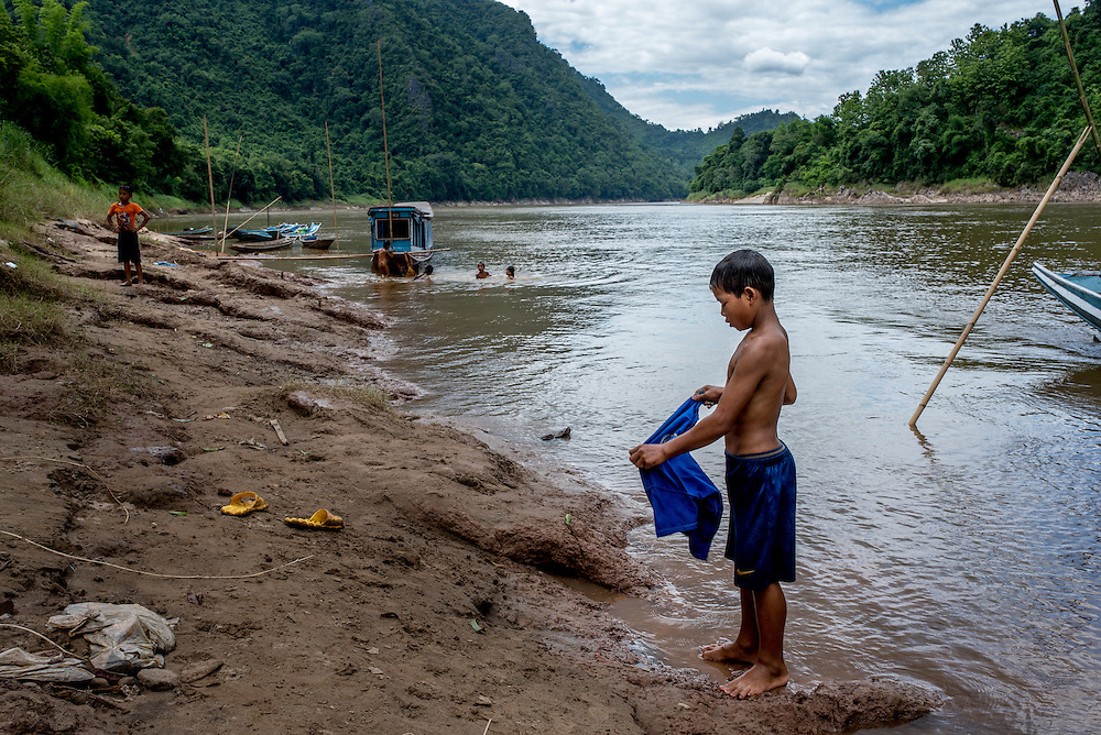 A boy puts on his shirt after washing it in the Mekong river near the village of Khoc Kham.