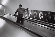 Teenager about to slide down escalator at Bond street station. London, UK, 1980s.