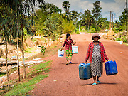 03 JUNE 2016 - SIEM REAP, CAMBODIA: Women carry their empty water jugs to a water distribution point in Sot Nikum, a village northeast of Siem Reap. Wells in the village have been dry for more than three months because of the drought that is gripping most of Southeast Asia. People in the community rely on water they have to buy from water sellers or water brought in by NGOs. They were waiting for water brought in by truck from Siem Reap by Water on Wheels, a NGO in Siem Reap. Cambodia is in the second year of  a record shattering drought, brought on by climate change and the El Niño weather pattern. There is no water to irrigate the farm fields and many of the wells in the area have run dry.     PHOTO BY JACK KURTZ