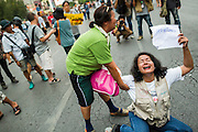 26 MAY 2014 - BANGKOK, THAILAND: Thai women collapse on Phaya Thai Road during a protest against the coup in Thailand at Victory Monument during a pro-democracy rally in Bangkok. About two thousand people protested against the coup in Bangkok. It was the third straight day of large pro-democracy rallies in the Thai capital as the army continued to tighten its grip on Thai life.   PHOTO BY JACK KURTZ
