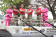 Michael Shinners from Sky Bet (left) and Racing UK presenter Tom Stanley (right) dressed in their pink suits pose with the Row 4 Victory Team at York Racecourse, York, United Kingdom on 13 July 2018. Picture by Mick Atkins.